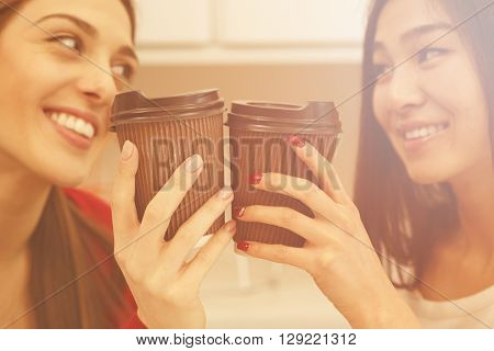 Toned image. Two women looking face to face in office, library, cafe or restaurant and drinking delicious coffee. Friendliness concept.