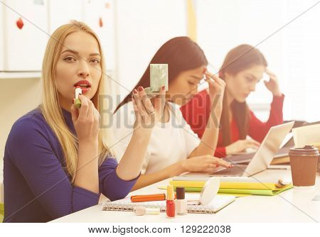 Closeup picture of student lady doing makeup and looking at camera while her groupmates or classmates preparing for lessons, classes or exams.
