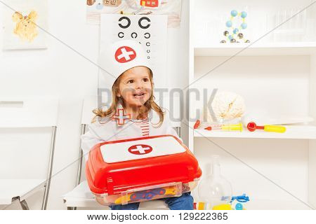 Cute little girl dressed like a doctor holding toy first-aid chest, sitting at the medical room