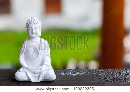 Ceramic Zen Buddha Statue Meditating with Blurred Texture Background. Yoga concept.