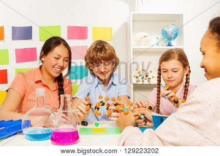 Four multi ethnic students studying chemistry with molecule model and flasks at the school laboratory