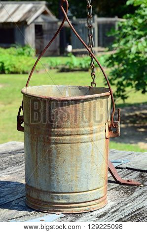 Old metal well bucket attached to a chain