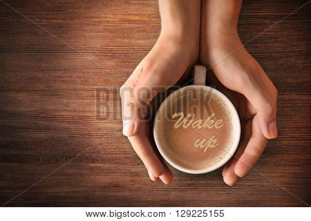 Female hands holding a cup of coffee with words Wake up on foam, top view