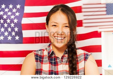 Beautiful smiling teenage Asian girl with long plait against  the flag of United states of America