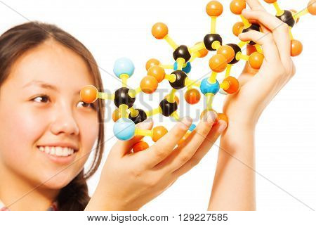 Asian teenage student, beautiful young girl with molecular model in her hands, isolated on white