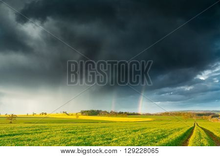 Dark Rainy Clouds and a Rainbow over British Spring Farm Land