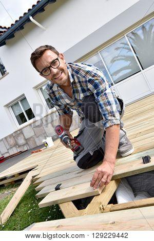 Smiling carpenter buidling wooden deck
