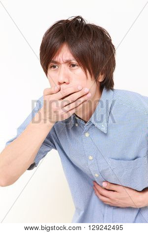 portrait of young Japanese manfeels like vomiting on white background