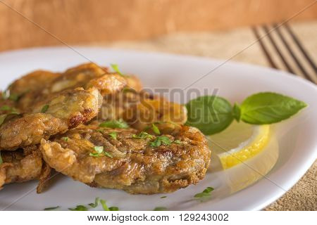 Fried pork brain with lemon and herbs on white plate ** Note: Shallow depth of field