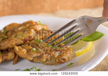 Eating fried pork brain with lemon and herbs on white plate