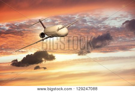 Brandless airplane flying in the clouds during sunset
