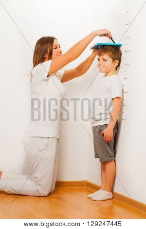 Mother measuring her son's height against the white wall, pointing the line with a pen, as kid standing at the floor