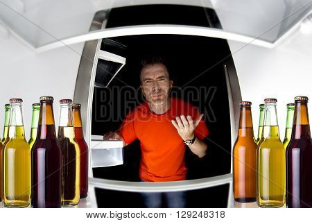 Man looking inside a fridge with bottles of beers late at night