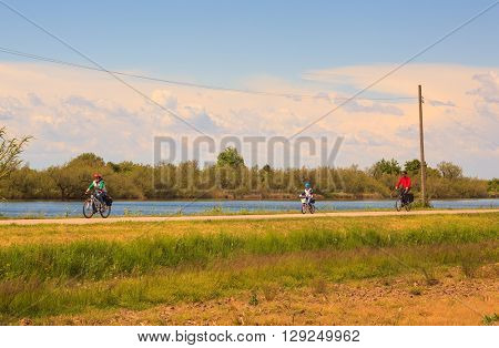 GRADO ITALY - APRIL 25: Dad and sons cycling in the Nature reserve of the Isonzo river mouth on April 25 2016