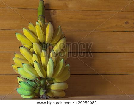 A banch of bananas and a sliced banana in a pot over a table;Fresh bananas on wooden background