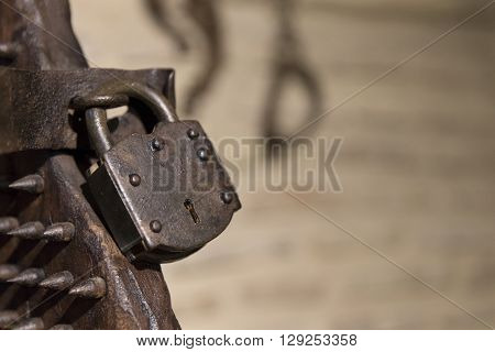 Close-up Of Iron Padlock Of Ancient Torture Chair In Sunlight