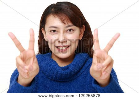 portrait of Asian woman showing a victory sign on white background
