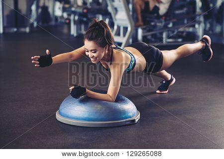 Asian sportswoman performing exercise on bosu ball