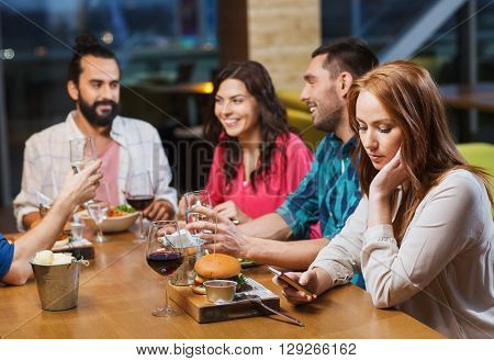 leisure, technology, internet addiction, lifestyle and people concept - woman with smartphone and friends at restaurant