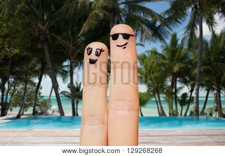 family, travel, summer holidays, tourism and body parts concept - close up of two fingers with smiley faces over exotic tropical beach with palm trees and pool background