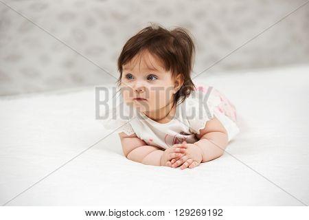 Portrait of baby girl crawling on blanket indoors