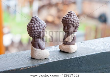 Teacher and follower or pupil ceramic little buddha. Buddhism, Yoga and meditation concept. ** Note: Shallow depth of field