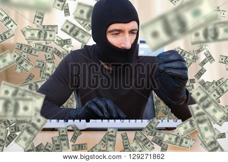 Burglar with balaclava hacking a laptop against light shining into living room
