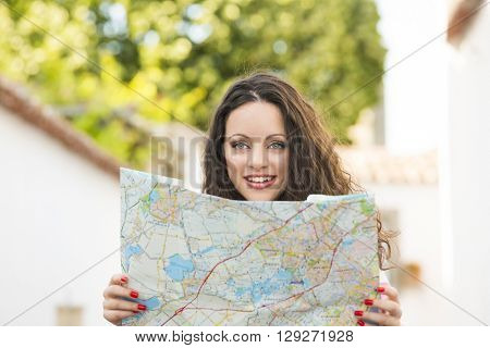 A beautiful female tourist searching a place on the map