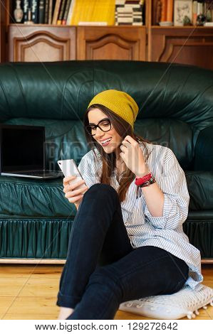 Hipster woman sitting on the floor using a laptop and mobile phone
