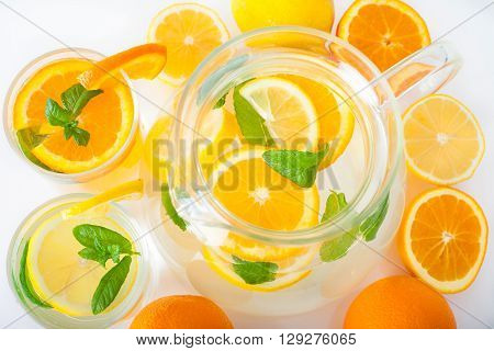 Preparation of the lemon and orange juice  in a jug with mint leaves