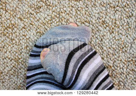 Closeup of striped socks full of holes