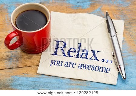 Relax, you are awesome - reminder or positive affirmation - handwriting on a napkin with cup of coffee