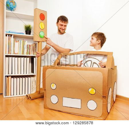 Dad explaining traffic regulations to his son, pointing to the green light signal, as they playing drivers with cardboard car at home