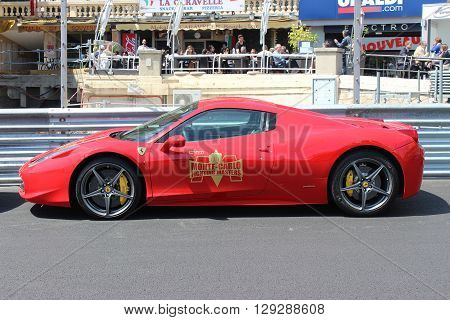 Monte-Carlo Monaco - April 28 2016: Red Ferrari 458 Italia Parked on the Street in Monaco. Guardrail of the Monaco Grand Prix in the Background