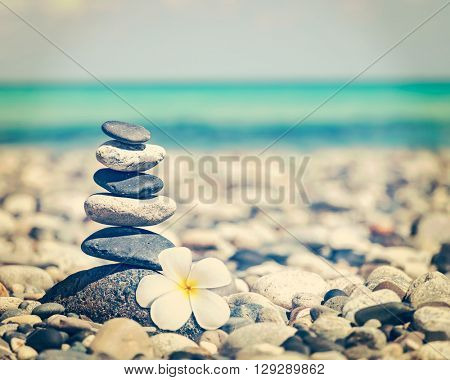 Zen meditation spa relaxation background - vintage retro effect filtered hipster style image of balanced stones stack with frangipani plumeria flower close up on sea beach