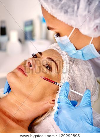 Woman middle-aged in spa salon with beautician. Beauty woman giving  injections. Anti-aging injections.