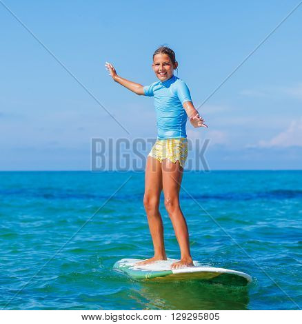 Teenage girl in blue has fun surfing