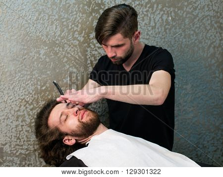 A Barber  Shaving Man's Beard