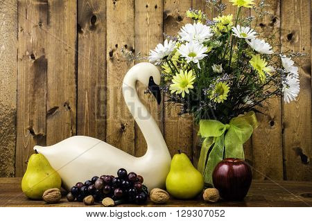 carved swan figurine and flower bouquet on wood background with fruits and nuts