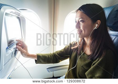 Woman watching movie on entertainment on plane