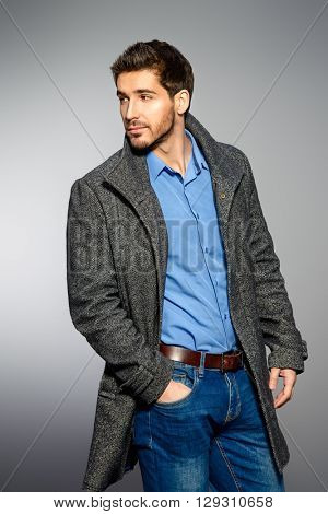 Handsome man wearing jeans clothes and a coat posing at studio. Men's beauty, seasonal fashion. Studio shot.
