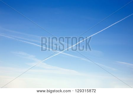crossing traces from an airplane. jet trail. background of clouds and condensation trails in the blue sky. copy space for your text