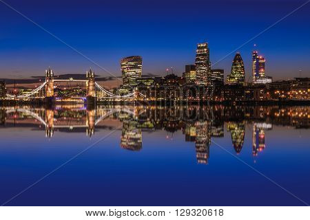 Modern London cityscape after sunset with reflections