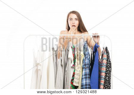 Beautiful suprised woman looking at camera while standing near clothes