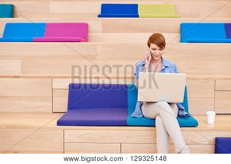 Pretty young woman with short modern hair, sitting in an open public space made up of wooden steps with colourful cushions, looking at her laptop screen while talking on her mobile phone