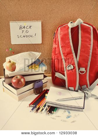 A red school back pack or book bag overflowing with school supplies