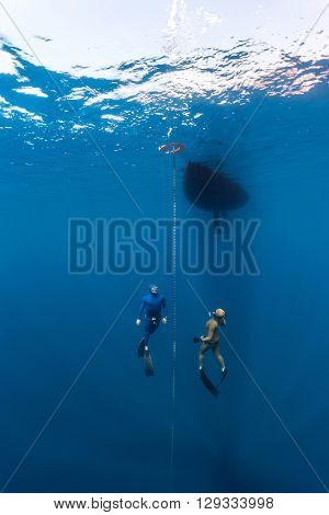 The underwater scenes. Two scuba divers swim under the water at the chain