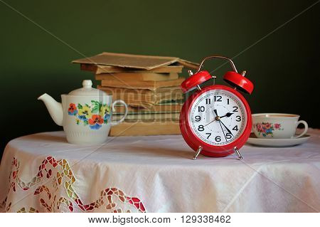 Red retro alarm clock on table with white tablecloth with lace. In the background a stack of books and an old teapot and teacup for tea. Retro still life with alarm clock.