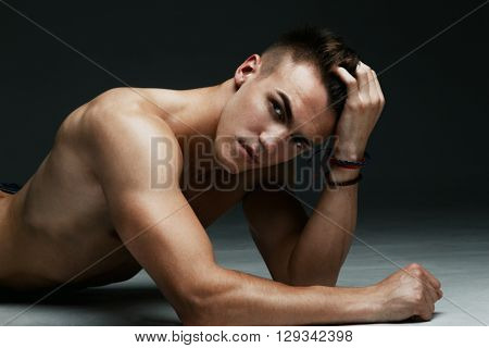 Young fashion topless man lying on the floor isolated on dark background. Strong Athletic Man Fitness Model.