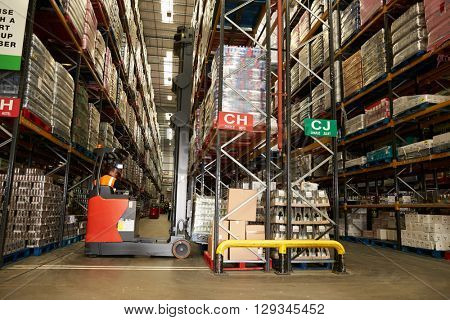 Man using aisle truck in a distribution warehouse, back view